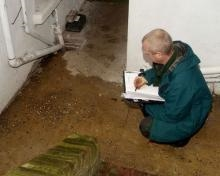 A pest control operative taking notes in a food facility.