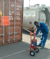 A pest control technician standing outside a cargo container operating fumigation equipment.