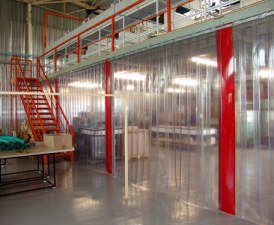 Plastic strip curtains splitting a large room in a warehouse.